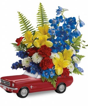 1965 Ford Mustang keepsake container holds yellow, red and blue flowers. Great for a guy's gift.