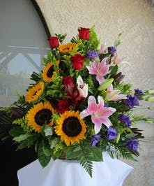 Basket filled with roses, sunflowers, purple lisianthus, pink stargazers and red safari.