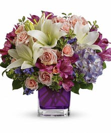 Various pastel flowers in a purple glass cube vase.