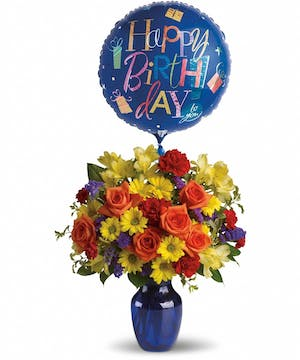 Orange, yellow and red birthday flowers in a blue vase with a Happy Birthday balloon.