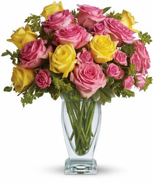 Yellow and pink roses with greenery in a clear glass vase.