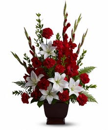 Sympathy tribute of red and white flowers with greenery.