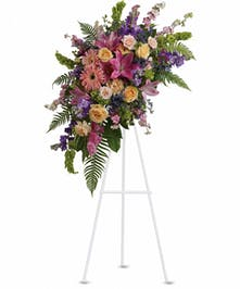 Sympathy spray of pink, purple and peach flowers with greenery.