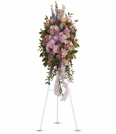 Sympathy spray of lavender, purple and pink flowers with pink organza ribbon.