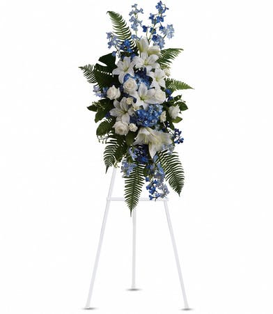Blue and white funeral flower spray on a standing easel.