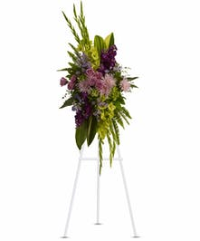 Sympathy spray of lavender flowers accented with greenery.
