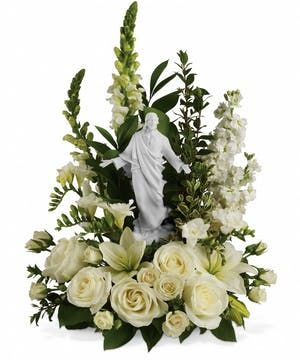 White flowers surrounding a porcelain sculpture of Jesus.