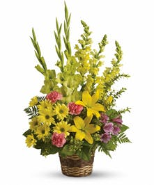 Bright sympathy basket of yellow and pink flowers.