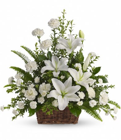 White lilies and other white flowers in a funeral/sympathy basket.