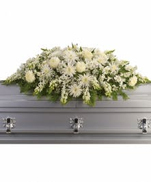 All-white casket spray of alstroemeria, snapdragons, chrysanthemums and more with greenery.
