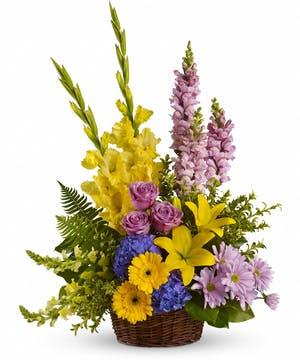 Sympathy basket of blue, lavender and yellow flowers with greenery.