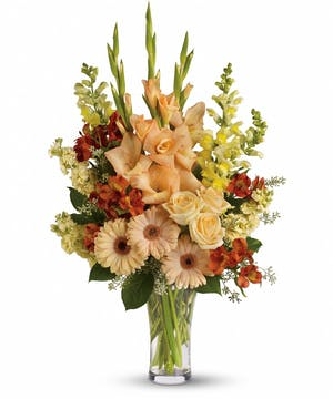 Sympathy bouquet of peach roses, gerberas, gladioli, orange alstroemeria, yellow snapdragons and more in a clear glass vase.