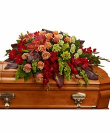 A magnificent casket spray with strong red, dark orange, and green toned flowers