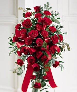 Sympathy spray of red roses and carnations with red ribbon.