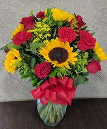 Sunflowers, roses and carnations in a clear glass vase tied with red ribbon.
