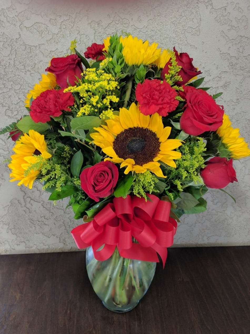 Sunny day bouquet with sunflowers roses carnations in rowland sunflowers roses and carnations in a clear glass vase tied with red ribbon izmirmasajfo