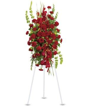 Sympathy spray of red roses, gladioli and carnations.