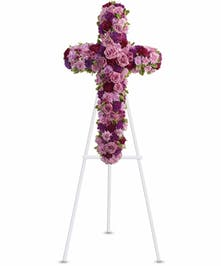 Sympathy cross of lavender and fuchsia flowers presented on an easel.
