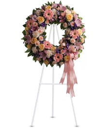 Sympathy wreath of peach roses, gerberas, carnations, pink lilies, and more with coordinating ribbon.