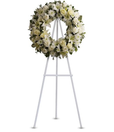 Standing wreath of all-white flowers on an easel for a funeral.