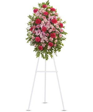 Hot pink and light pink flowers in a funeral spray.