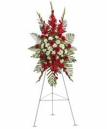 Sympathy spray of red and white flowers with greenery.