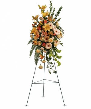 Sympathy spray of peach roses and lilies, orange roses and alstroemeria, and more.