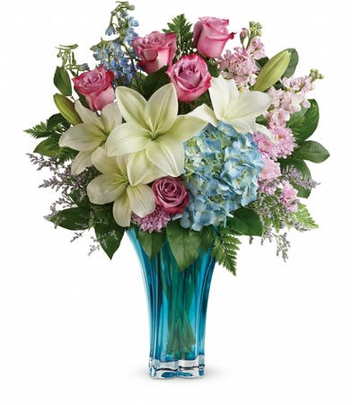 Blue hydrangea, white lilies, blue delphinium, pink stock, lavender cushion spray chrysanthemums and more in a blue glass vase.