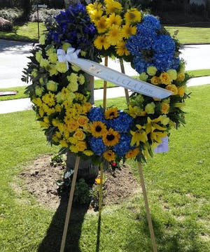 Sympathy wreath of blue and yellow flowers suitable for a memorial service.