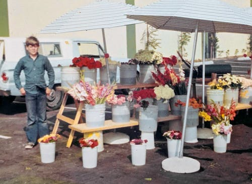 A young helper lends a hand at the flower booth in the late 70s