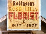 A wooden sign promotes Robinson's Rose Hills Florist and Gift Shop